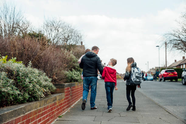 Walking home from School Rear view of a mature man walking down the street with his children. He is holding his sons hand and carrying his baby daughter. stay at home father stock pictures, royalty-free photos & images