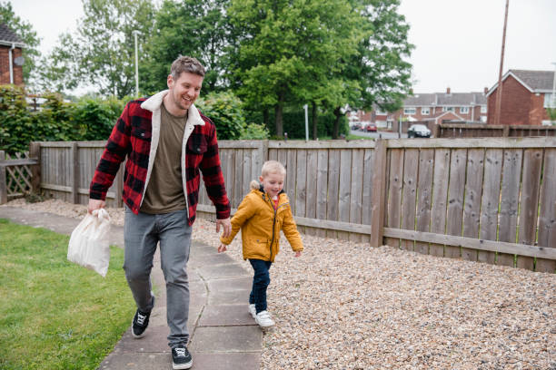 Walking Home with Dad Little boy holding his fathers hand as they walk along the garden path to get back to the house. They are smiling and laughing on the way back. stay at home father stock pictures, royalty-free photos & images