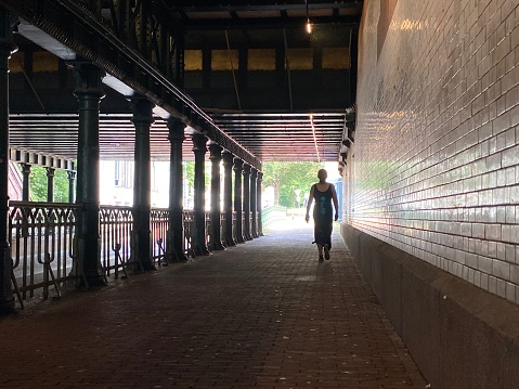 Woman walking in a city tunnel