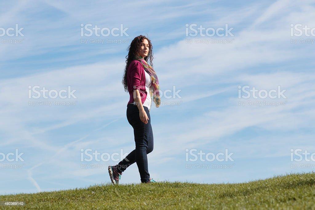 Walking along grassy horizon beautiful shapely Canadian outdoor girl stock photo
