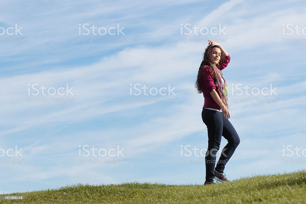 Walking along grassy horizon beautiful shapely Canadian outdoor girl royalty-free stock photo