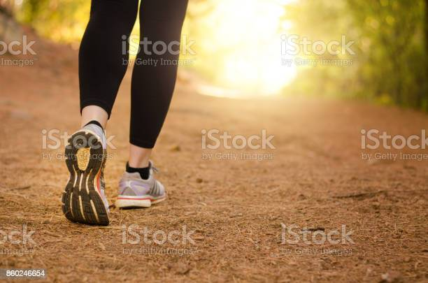 Pair of legs walking on a trail in nature towards the light