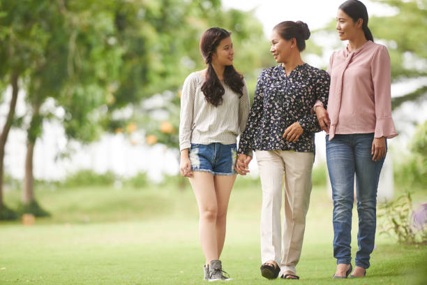 Walking in park Cheerful Vietnamese teenage girl with her mother and grandmother walking in park vietnamese ethnicity stock pictures, royalty-free photos & images
