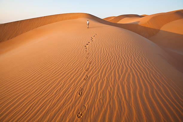 ходьба в песчаные дюны с ног принтом - oman стоковые фото и изображения