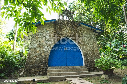 stone church in the middle of the forest. Blue door