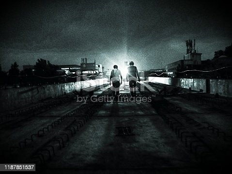 Silhouettes of people walking on a bridge