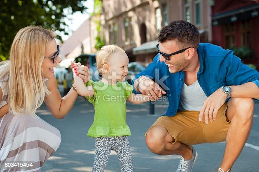 Cute baby girl is practicing walking with her happy and smiling parents during the perfect summer day.