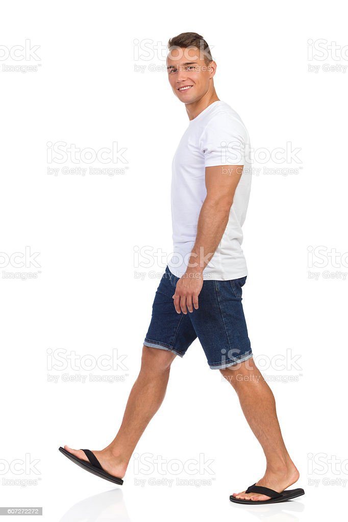 Walking Man In White T-shir And Looking At Camera. stock photo
