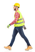 Walking construction worker in yellow helmet and lime reflective waistcoat. Full length studio shot isolated on white.