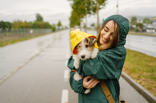 Photo of a young woman and her puppy having fun outdoors on a rainy day.
