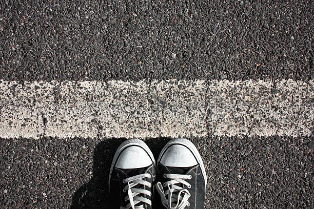 Walking obstacle People shoes standing on the asphalt with white line. boundary stock pictures, royalty-free photos & images