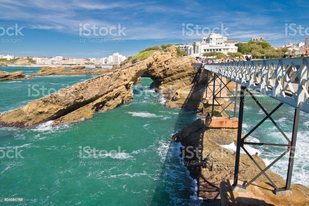 walking on beautiful footbridge leading to rocher de la vierge on atlantic coastline with cliffs and turquoise ocean in biarritz, basque country, france stock photo