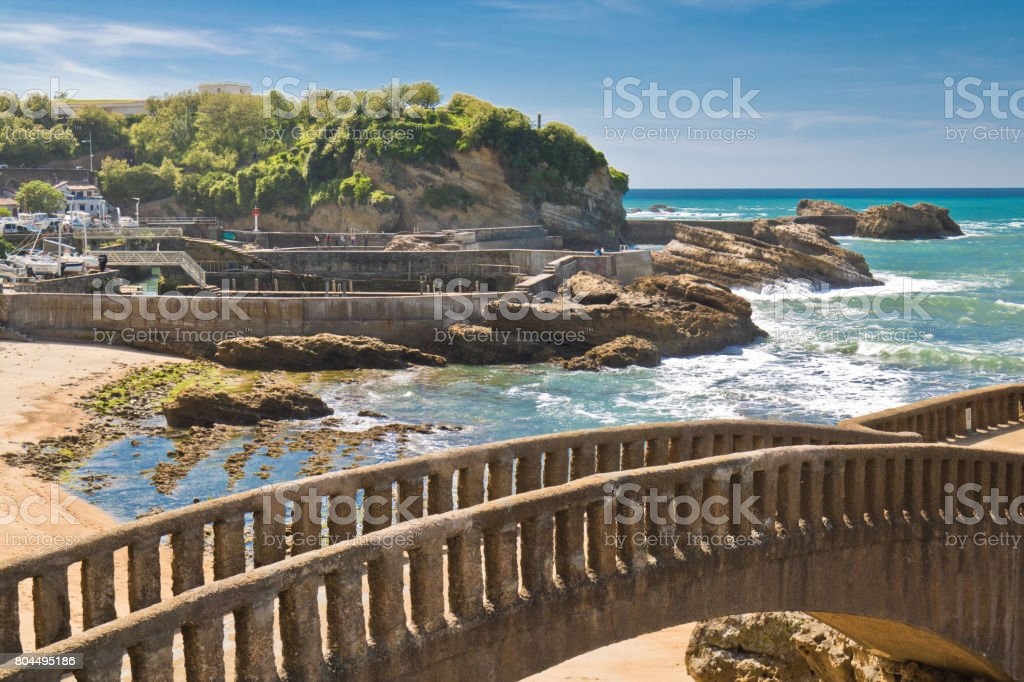 walking on footbridge leading to cliff island over sandy beach in touristic destination surf spot with turquoise ocean and waves in biarritz in blue sky stock photo
