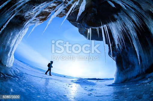 Hiker on the frozen Lake Baikal as seen from inside a cave on Olkhon Island.