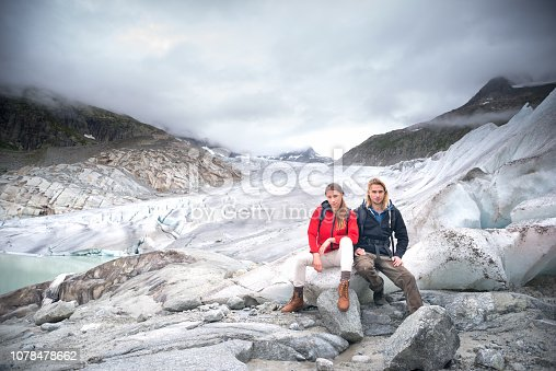 Mountain walking couple sitting on the edge of a glacier that is retreating due to global warming, or climate change. Shot on the Rhone Glacier in the Swiss Alps.