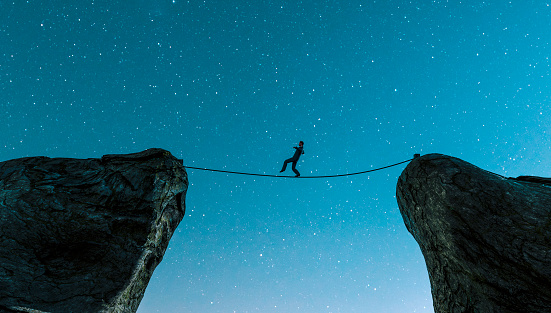 Man walks carefully on a rope that has been tied between two cliffs. He risks falling to the ground. Concept of success and avoiding problems following a career path.  Note: The man is a 3D-render. Model release attached.