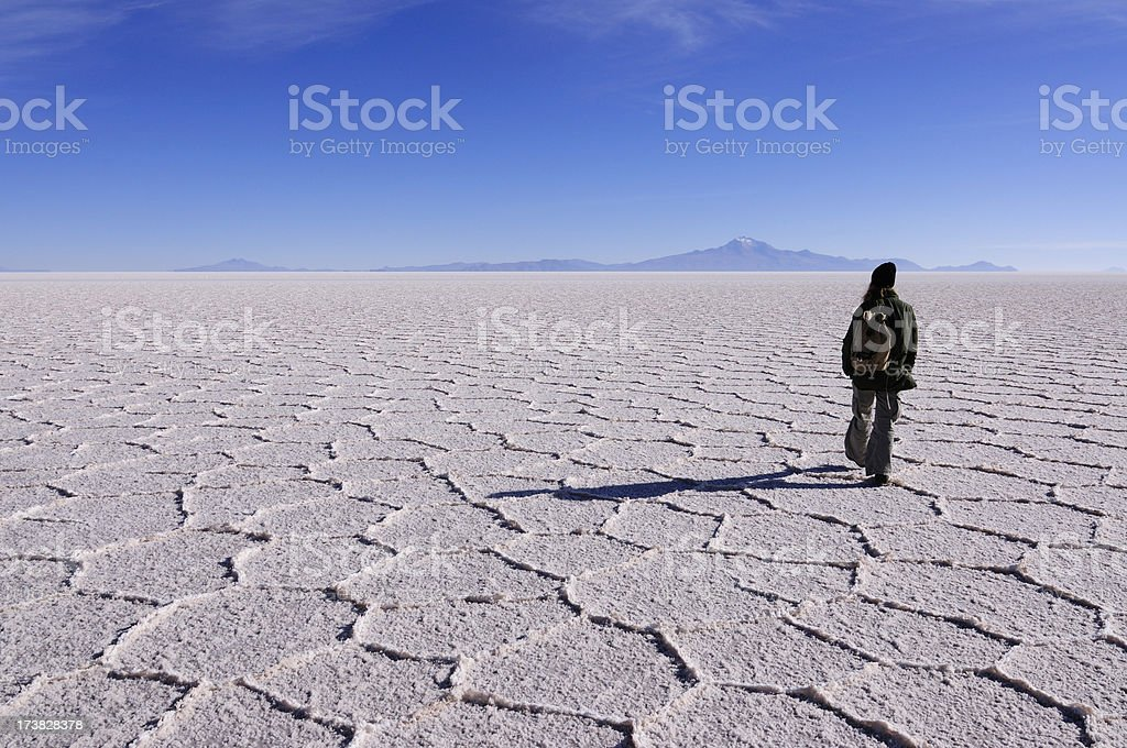 Walking on Salt Flats of Uyuni in Bolivia stock photo