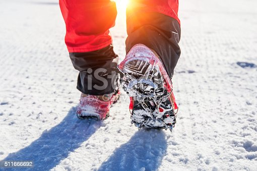istock walking on snow with Snow shoes and Shoe spikes. 511666692