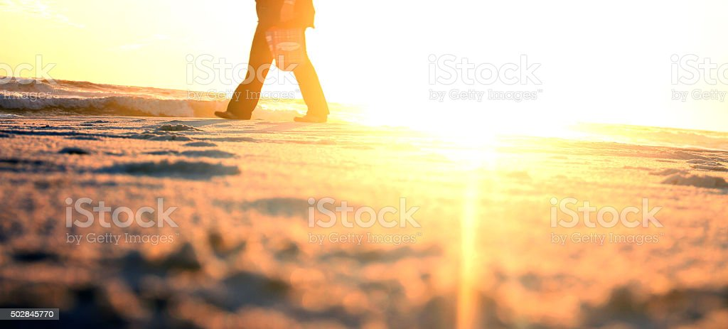 Walking on the beach back light when sun is setting stock photo