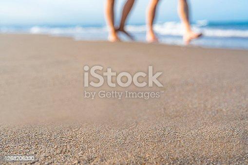 Horizontal seascape of woman walking barefoot on clear Sandy beach in long pink floral skirt on Ballina beach NSW Australia