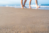 Summer backgrounds: blurred couple walking on the beach. Useful copy space available for text and/or logo. Predominant color is blue. High resolution 42Mp studio digital capture taken with SONY A7rII and Zeiss Batis 40mm F2.0 CF lens