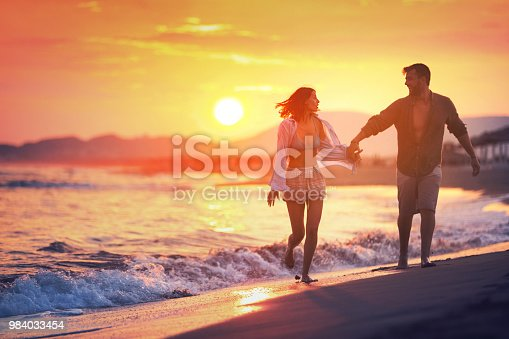 Closeup front view of mid 20's couple walking on a beach on a beautiful summer sunset. They are having fun and enjoying their vacation. 4k, good for grading.