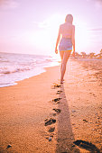 Young woman walking on the sand and leaves footprints