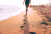 Woman walking on the sand and leaves footprints