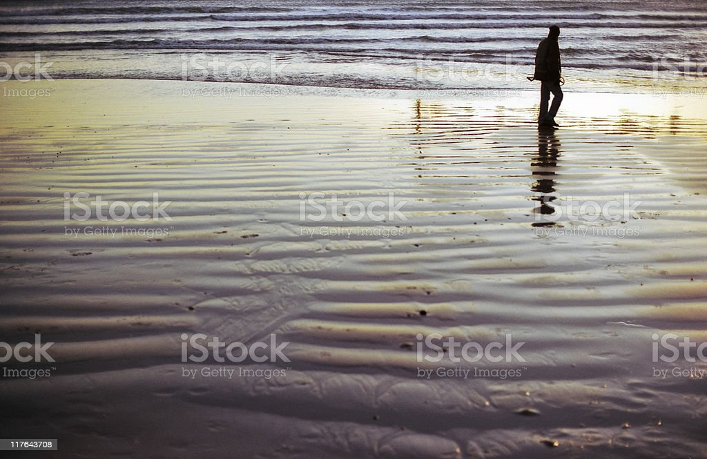 Walking (almost) on the sea - man on wet beach stock photo