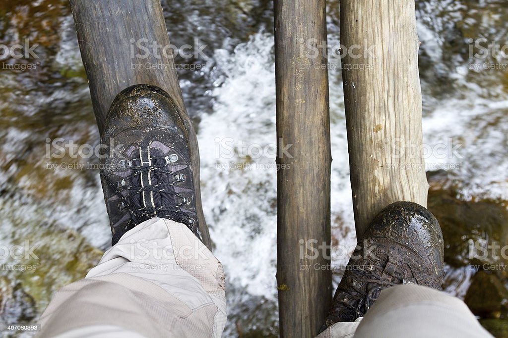 Walking over a swing bridge stock photo