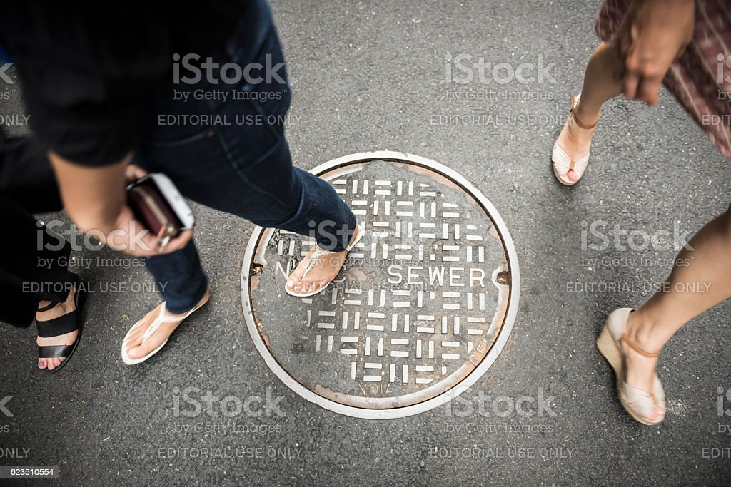 Walking over New York City sewer manhole cover stock photo