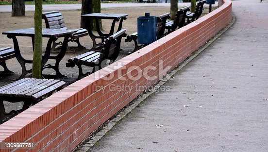 istock walking path through the park where there is also a bowling court made of a beige sandy surface in the shape of a rectangle. a number of benches without backrests are used to relax the audience 1309667751