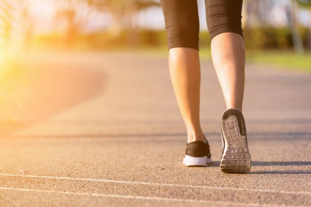 Walking. Young asian women walking on a running track.relaxing and exercise concept. human leg stock pictures, royalty-free photos & images