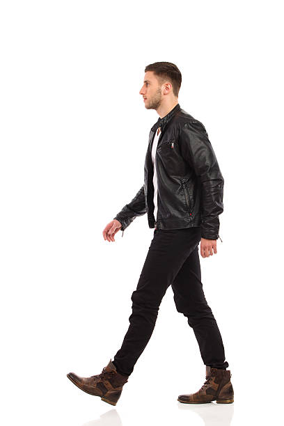 Walking rock man. Walking man in black leather jacket and black jeans. Full length studio shot isolated on white. leather jacket stock pictures, royalty-free photos & images
