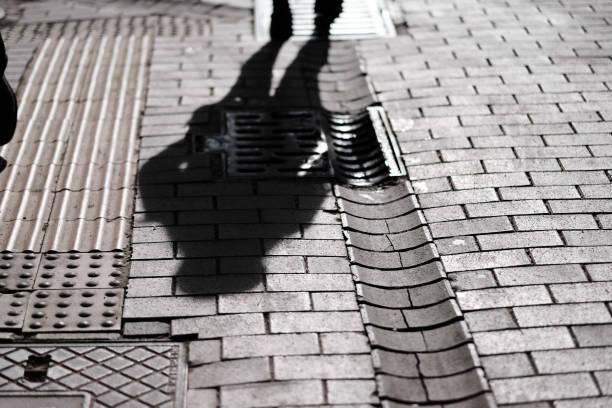 石畳の上を歩く影 - 背景に人 ストックフォトと画像