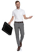 istock walking smart casual man with briefcase is welcoming 1131990235