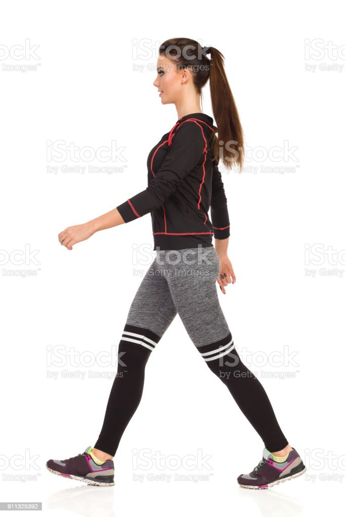 Walking Smiling Young Woman In Sports Clothes And Striped Leggings. Side View. stock photo