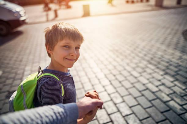 walking sohn zur schule - taschen von liebeskind stock-fotos und bilder