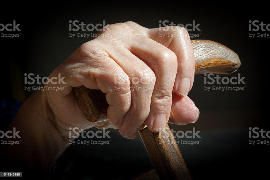 walking stick in hand of senior woman stock photo