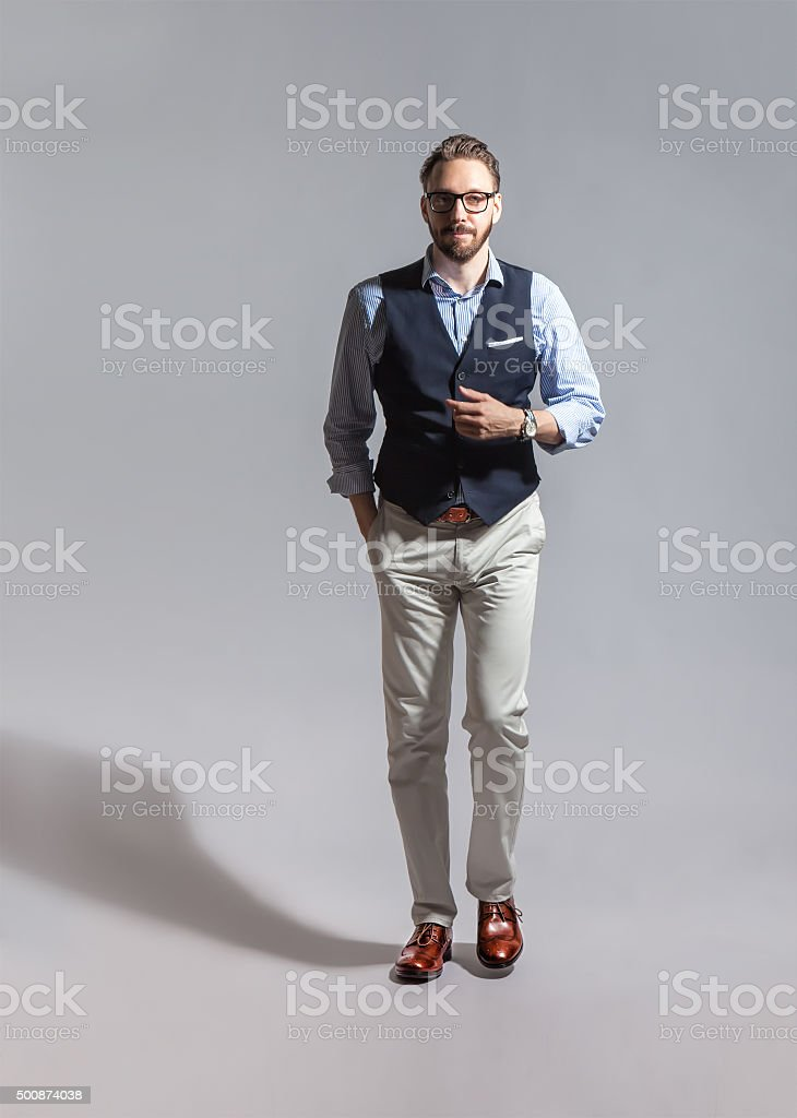 Walking suave stylish bearded man in classic vest stock photo