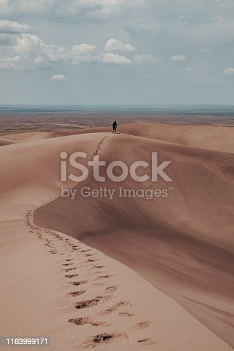 A man leaving footprints in the giant sand dunes at Great Sand Dunes National Park in Colorado, USA.