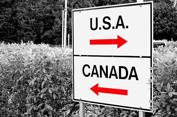 Walking the Line A shot of a sign at the US/Canadian border geographical border stock pictures, royalty-free photos & images