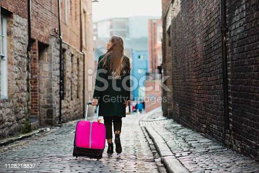 A rear view shot of a caucasian woman walking down a cobblestone pathway in a narrow street, she is wearing warm clothing and pulling a suitcase.