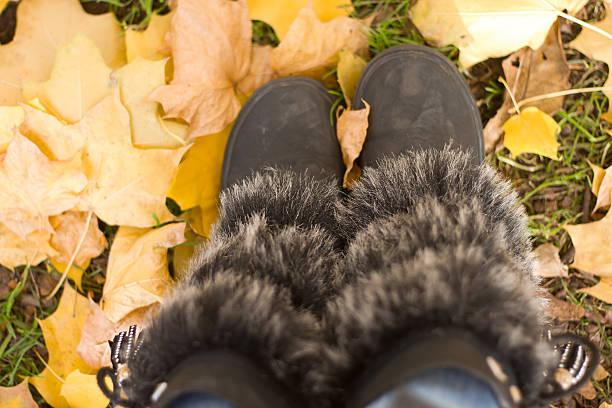 fuß durch den herbst blätter, nahaufnahme - lammfellstiefel stock-fotos und bilder