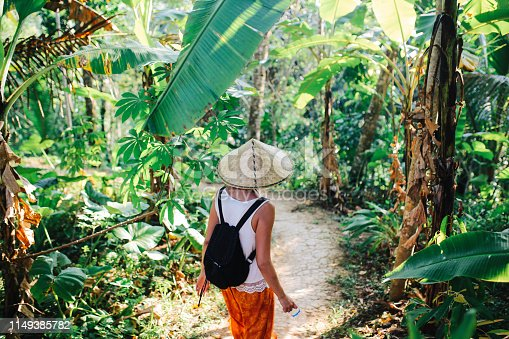 Tourist woman enjoying the walk through Bali, Indonesia, among the bamboo trees. Tourism, traveling concepts in Southeast Asia, Indonesian culture.