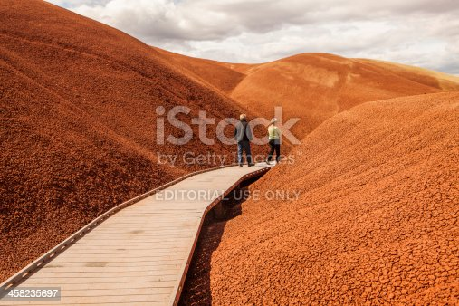 Mitchell, Oregon, USA - June 9, 2012: A man and woman walking on the boardwalk through the Painted Hills of central Oregon, which are part of the John Day Fossil Beds National Monument.