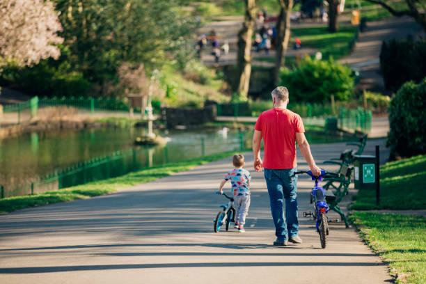 zu fuß durch den park mit seinem sohn - fahrradträger stock-fotos und bilder