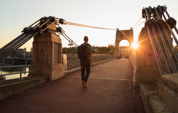 Walking toward the sun Man walking over the Passerelle du College footbridge during sunset. Lyon, France. footbridge stock pictures, royalty-free photos & images