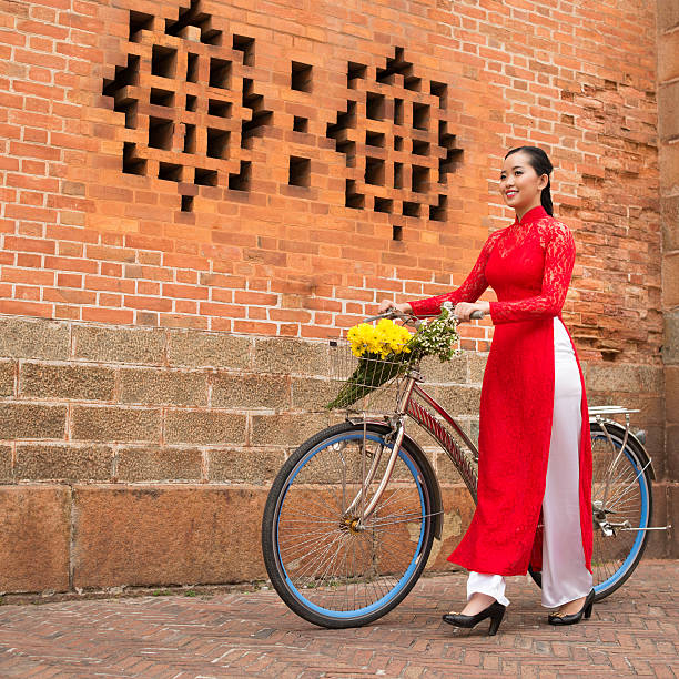 walking with bicycle - ao dai stock photos and pictures