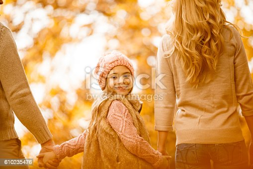 658444674istockphoto Walking with parents in autumn park 610235476